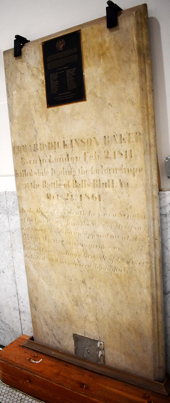 Large, stone grave marker standing on a base in the Baker County Courthouse. Image courtesy of Lisa Britton.