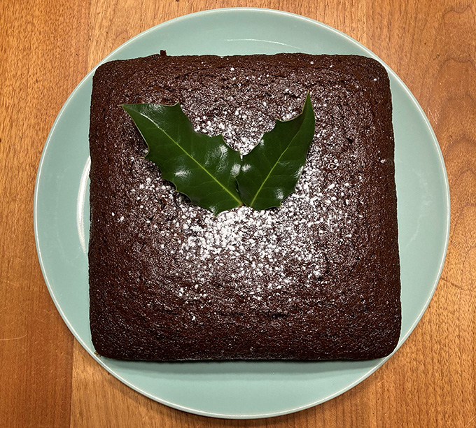 Color photograph of a square cake on a green plate. The cake is topped with two holly leaves.