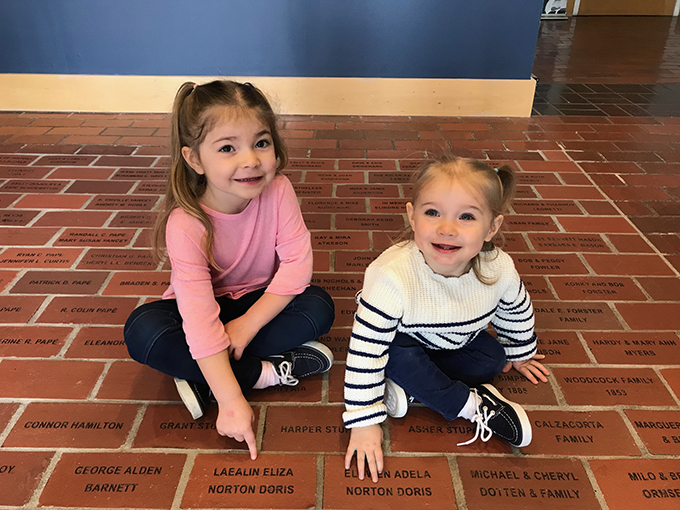 Arleen Barnett's granddaughters, Laealin and Elowen, pose with their bricks after seeing them for the first time.