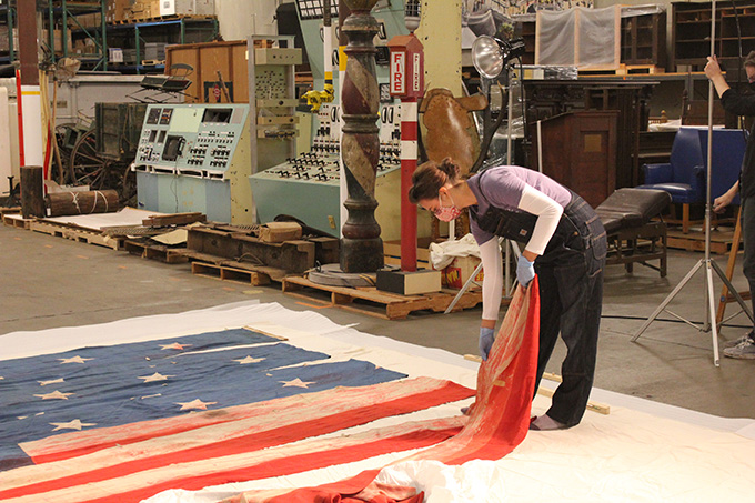 "OHS Museum Cataloger Kathleen Daly arranges the U.S.S. ""Oregon"" pennant on a muslin covered ethafoam sheeting. Photograph by Silvie Andrews."