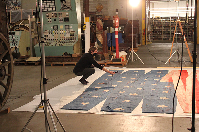 "Digital Services Photographer Robert Warren tests lighting before photographing the U.S.S. ""Oregon"" pennant. Photograph by Silvie Andrews."