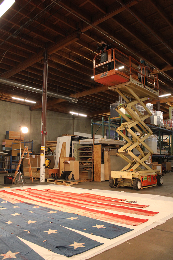 "OHS staff use a scissor lift to photograph the U.S.S. ""Oregon"" pennant. Photograph by Silvie Andrews."
