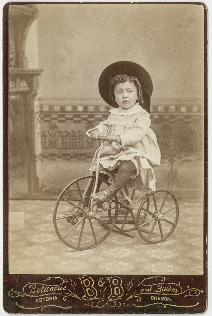 Child wearing a hat and riding a tricycle in about 1885. OHS Research Library, OrHi 72983
