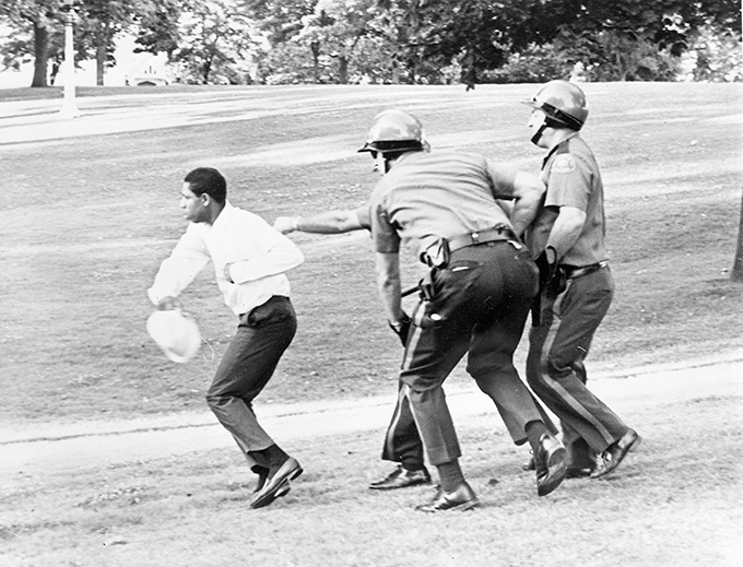 A man is chased by three Portland policemen during the 1967 Irving Park riot in Albina. OHS Research Library, bb005808