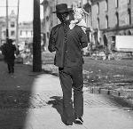 Father and son walk in Portland's Chinatown, ca. 1895. Most male Chinese immigrants, whether they were laborers, merchants, or houseboys, wore a long braid with silk woven into the ends, called a queue. OHS Research Library, OrHi 28159, bb016093