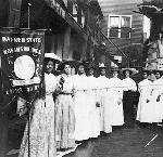 Nine African American women posed, with Nannie Burroughs holding banner reading,