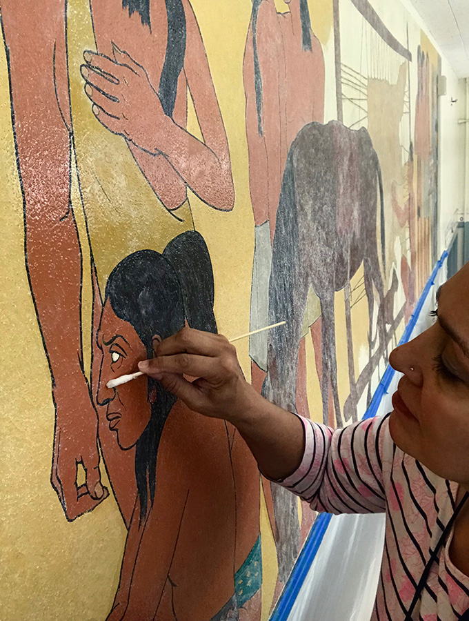 Conservator Nina Olsson removes overpaint from New Deal-era mural at Abernethy Elementary School. Photograph courtesy of Heritage Conservation Group.
