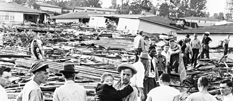 Carl Downey carries an unidentified woman to safety after rescuing her from a rooftop during the Vanport Flood.  Taken by Mel Junghan on May 31, 1948 in Portland, Oregon. OrHi 3623