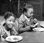 Children at the Black Panthers' free breakfast program, 1971. Kent Ford sits with the children.