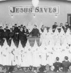 Ku Klux Klan members share a stage with members of the Royal Riders of the Red Robe, circa 1922, probably in Portland. OrHi 51017