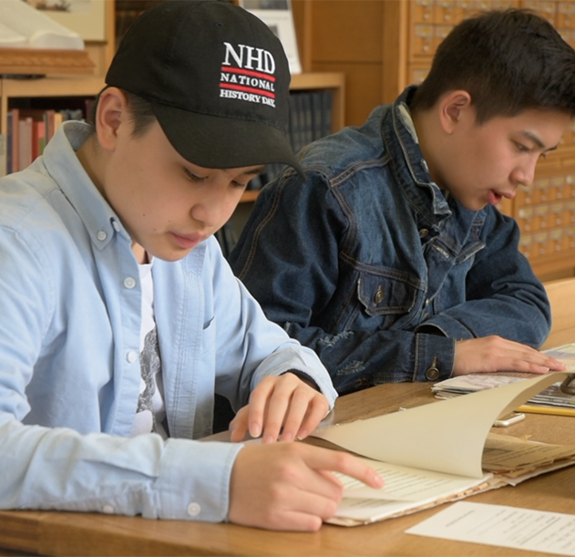 Oregon History Day participants Alan Zhou (left) and Kyler Wang (right) looking at primary documents in the OHS Research Library.