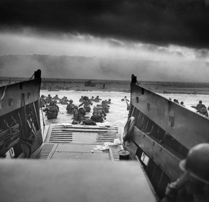 U.S. Army troops exit a landing craft during the D-Day landing in Normandy, France. June 6, 1944, National Archives and Records Administration, 26-G-2343