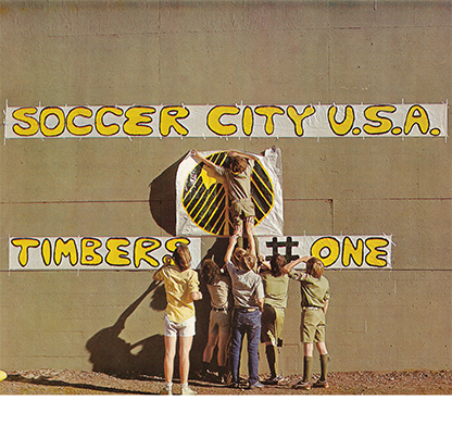 Young Timbers supporters and Boy Scouts hang banners on the outfield wall at Civic Stadium in this photo published in Kick Magazine, 1975. OHS Research Library, Coll 160.
