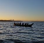 CTCLUSI on Canoe Journey traveling through the Puget Sound with the sunrise in the background. Photo Taken by Tribal Biologist and Coos Tribal Member, John Schaefer. Image courtesy of Jesse Beers.