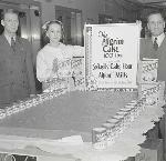 Portrait showing three unidentified people, probably employees, with a huge cake displayed at Meier & Frank in Portland. OHS Research Library, Oregon Journal Negative Collection; Org. Lot 1368; Box 372; 372A948