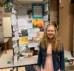 "Seven Peaks School student Emily Gerber stand by her exhibit, ""Painting the Way: The Story of Tyrus Wong."" Image courtesy of Emily Gerber."