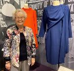 Governor Barbara Roberts poses in the Oregon Historical Society's Nevertheless, They Persisted exhibition next to her inauguration dress.