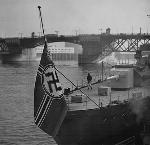 "The German cruiser ""Emden"" chugged down the Willamette River with the Nazi naval flag, or ensign, at the stern. The ship moored in Portland at the foot of West Couch Street. OHS Research Library, Oregon Journal collection, bb017448"