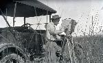 William L. Finley photographing beside his car near Island Ranch, Harney County, Oregon, 1919. Org. Lot 369, Finley D1991.