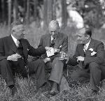 Three men in suits drinking whiskey in a field - Oregon, date unknown. Oregonian Photo Collection, Nitrate Box 1, unknown negatives.