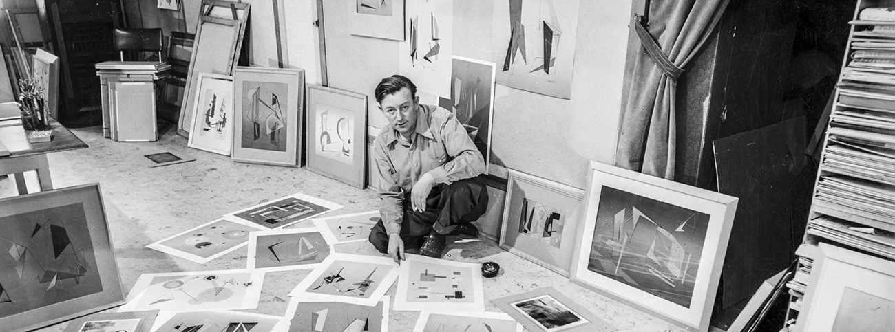 Albert Patecky, Portland artist, in his home studio surrounded by his work as he selects some for a show. July 29, 1951, photo by William Grand. Oregon Journal collection, 013364