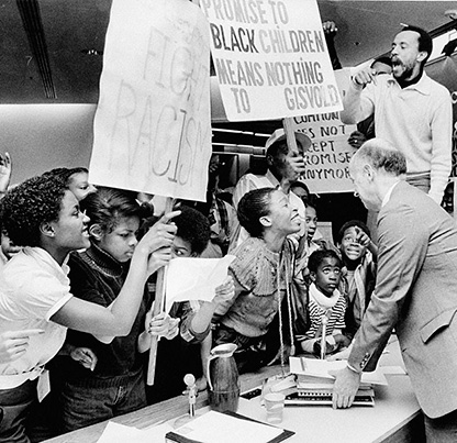 Black United Front leader, Ron Herndon, stands on a desk at a School Board protest against the closure of Harriet Tubman Middle School, March 30, 1982. Steve Nehl, Oregon Journal. OrHi 95005 ba018353