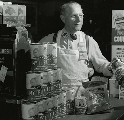 Fred Meyer poses for an advertisement photo checking out groceries,  circa 1950. Ackroyd-Marks Studio Coll 199 b7.f2 ba026202