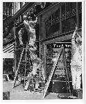 Workers remove the Art Deco aluminum grills decorating the front of the Fred Meyer store on SW 6th Avenue and Morrison in downtown Portland in order to donate the metal to the war effort, 1940. Coll 199