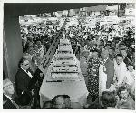 Gateway grand opening cake cutting celebration. Fred Meyer, Eva Meyer and Peter Mudie stand by the cake as it is cut with the ceremonial giant knife. Coll 199 b14.f2