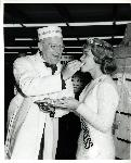 Fred Meyer feeds cheese to the Clark County Dairy Princess at the opening celebration of the Hazel Dell store. The cheese was a giant wheel of cheddar specially made in Wisconsin for the store opening. Coll 199 b16.f1