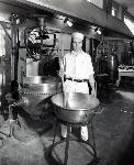 Man stands in Fred Meyer candy kitchen with a huge spoon surounded by large mixers and bowls. Coll 199 b10.f2