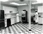 Two women work at the Fred Meyer dairy plant test kitchen. Coll 199 b10.f5