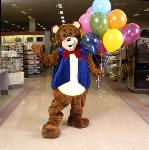 Fred Bear mascot poses with balloons in a Fred Meyer store. Coll 199 b34.f5