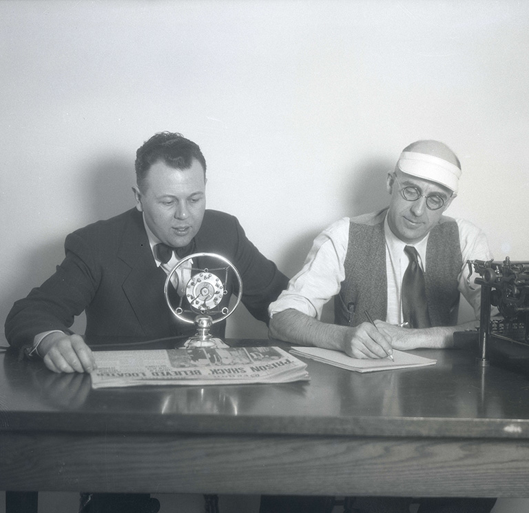 Crookham and Kirkhan at table with microphone and typewriter. Oregon Journal Negative Collection; Org. Lot 1368; Box 371; 0371N619