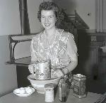 1942 Portland Rose Festival Princess Shirley Fowler posing with baking ingredients. OHS Research Library, Oregon Journal Negative Collection; Org. Lot 1368; Box 375; 375A0286