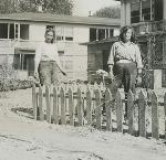 Agnes and Delores Skovgaard standing behind a picket fence in front of their apartment in Vanport, Oregon. They are sorting through personal items after residents were allowed back into Vanport following the Vanport flood. Org. Lot 1364, bb014270
