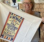 OHS member and Nevertheless, They Persisted exhibit sponsor Mary Fellows holds a woman suffrage tea towel in her home.